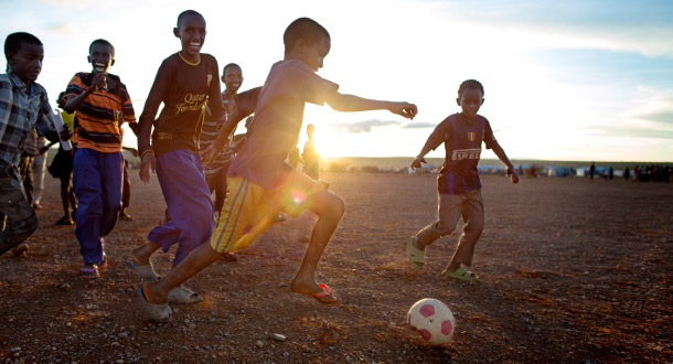A group of boys playing football on a dusty patch of land as the sun sets.