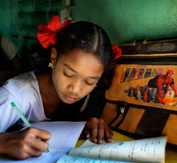 A young girl with pig tails and red ribbons in her hair doing school work.
