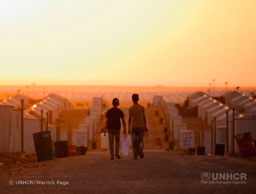 Image of two boys walking thru a refugee camp in the sunset. ©UNHCR/Warrick Page