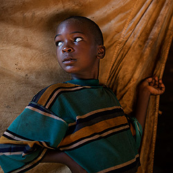 An African boy standing outside a shelter in a refugee camp.
