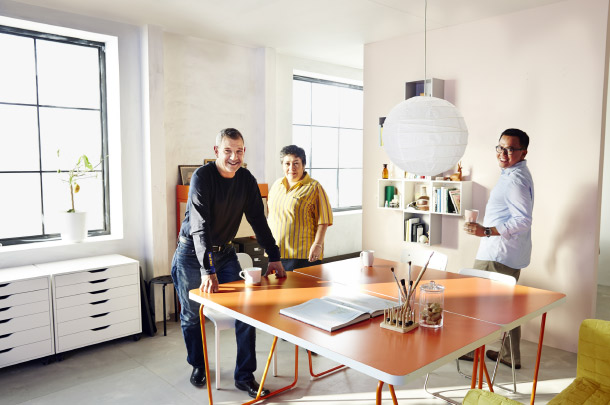 Three IKEA co-workers in a room setting consisting of two orange desks with chairs, a white chest of drawers and open wall shelves.