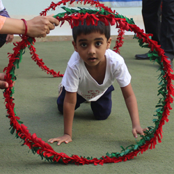 A young boy crawling through hula hoops that are covered with red and green ribbons.