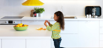 A young girls peels an orange in a kitchen filled with products that make it easier to live more sustainably