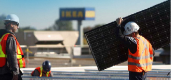 Two men install solar panels on the roof of an IKEA store