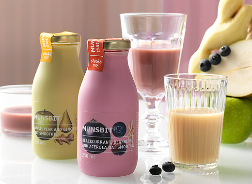 Display of two bottles with apple/pear and blackcurrant/blueberry oat smoothies, shown together with glasses filled with smoothie.