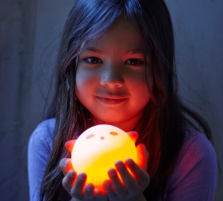 Girl holding a SPÖKA LED night light that is turned on and off by pressing the ghost's head