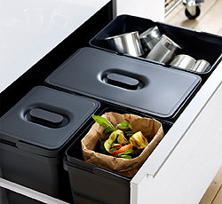 A kitchen drawer with black waste sorting bins with lid, two large and two small, here used for recycling cans, food waste, paper and plastic.