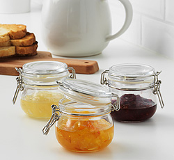 Three small preserving glass jars filled with different kinds of chutney.