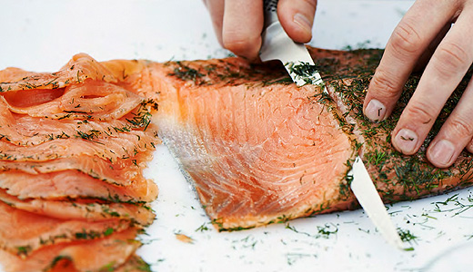A person cutting thin slices of marinated salmon.