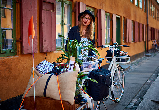 A woman standing outside a house with her bicycle and a crammed trailer with boxes, a suite case and a green plant.