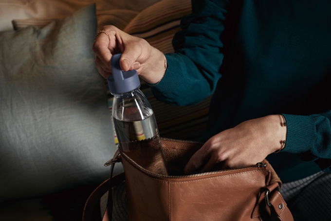 A reusable IKEA 365+ plastic bottle being picked up from a brown leather bag.
