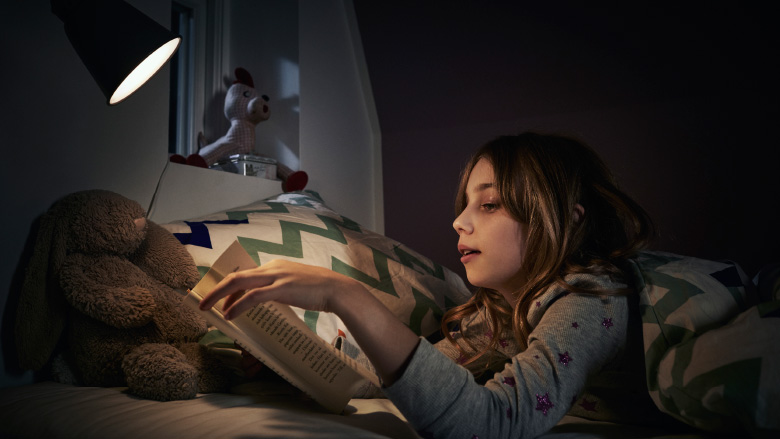 Young girl wearing grey sweater lying in bed at night reading a book under a light