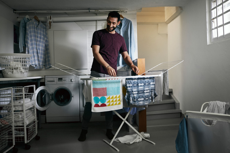 A man hanging laundry in the basement using the drying rack MULIG