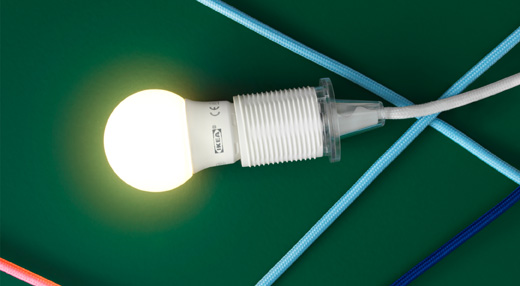 Close-up of a lit LED bulb on a green background.