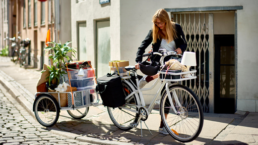 A bicycle with front rack, rear rack with bags and a trailer filled with boxes, grocery bags and a green plant.