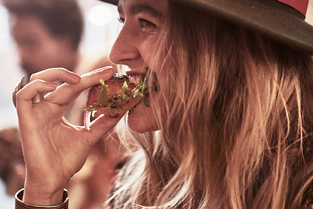 A woman taking a bite of a pulled salmon sandwich.