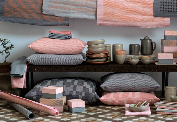 A collection of cushion covers, bowls, plates, gift boxes and wrapping paper in light pink and grey.