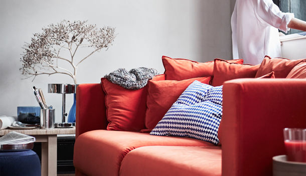 Close-up of a three-seat sofa with an orange velvet cover and lots of cushions.