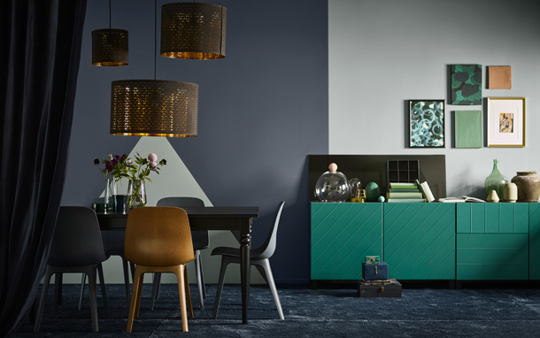A side-by-side blue dining room and green living room from IKEA for darker interior design ideas kept soft with pops of brass details, lighter tone-in-tone colours and felty textures.