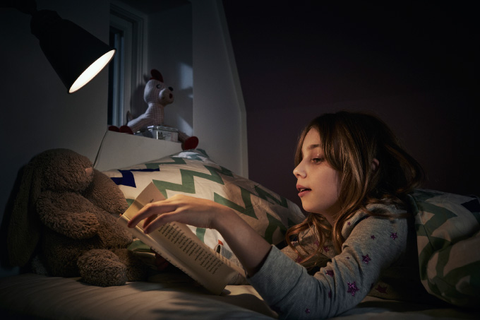 A girl wearing pajamas lying in bed at night reading a book using a night light.