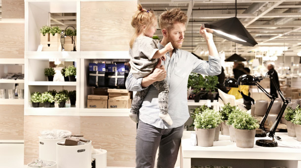 A father with his young daughter looking at an IKEA PS 2012 pendant lamp at the IKEA store.