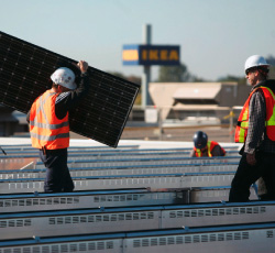 Two workmen installing solar panels on the roof of an IKEA store