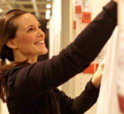 A photo of a store co-worker organising curtains at an IKEA store