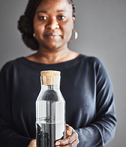 A woman holding a glass carafe with a cork lid.