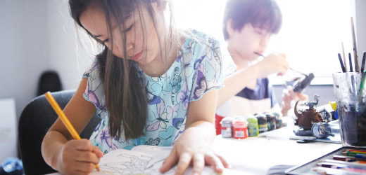 a young girl and boy drawing and painting at a desk