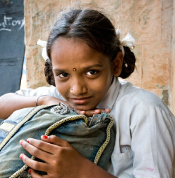 A photo portrait of a young Indian girl in a classroom