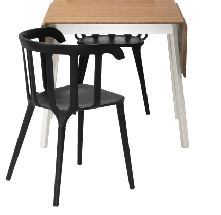 A bamboo surface table with white legs and two black wood plastic composite chairs
