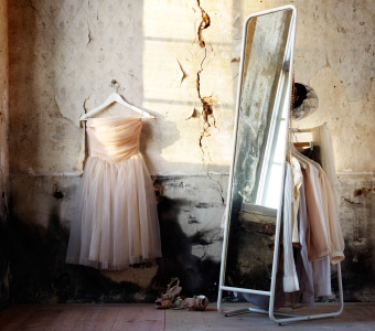 KNAPPER, standing mirror with clothes hanging behind it, and a beige ballerina dress hanging against a cracked cement wall.