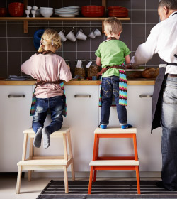 Adult man in apron, and two kids standing on top of stools to reach the countertop in a kitchen.