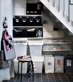Storage boxes in black and white incorporated underneath a staircase.