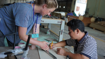 Female in blue t-shirt working on IKEA factory floor in Vietnam with male in a striped t-shirt.