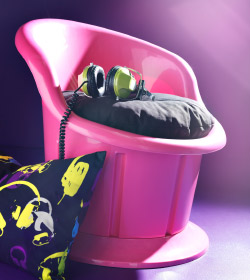 Close up of pink POPPTORP armchair with black seat cushion, and headphones laying on top.