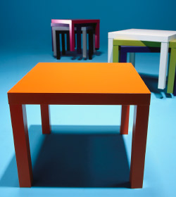 Close up of orange LACK table, standing with different coloured LACK tables stacked on top of each other in the background.