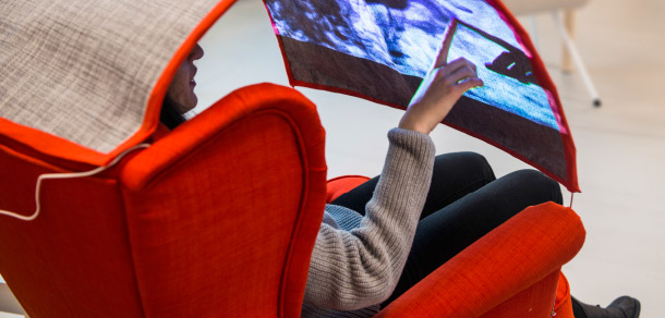 Close up of person sitting in a red armchair with a built in interactive screen.