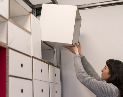 Female in grey sweater placing a white storage unit into a wall made out of many storage units.
