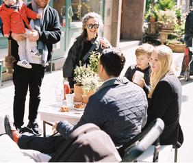 A group of people gathered outside around a table having a cup of coffee.