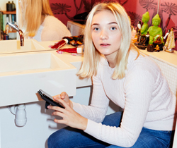 A young woman sitting in the bathroom, looking into the camera while holding her mobile phone.