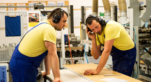 Two men wearing yellow t-shirts, headphones and blue dungarees, standing in a factory producing IKEA furniture.