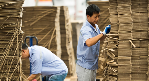 Two men in blue shirts, inspecting high piles of cardboard boxes.