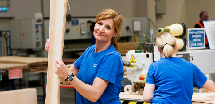 Two women in a factory producing IKEA furniture, one of the women is holding a side panel in birch veneer.