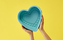 A person holding a light blue, heart-shaped baking mould.