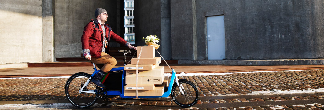 Stack of IKEA boxes on a delivery bike being ridden by a man in glasses