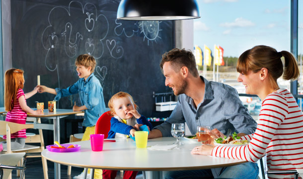 A mother, father and young child eating together in an IKEA restaurant with two children playing in the background