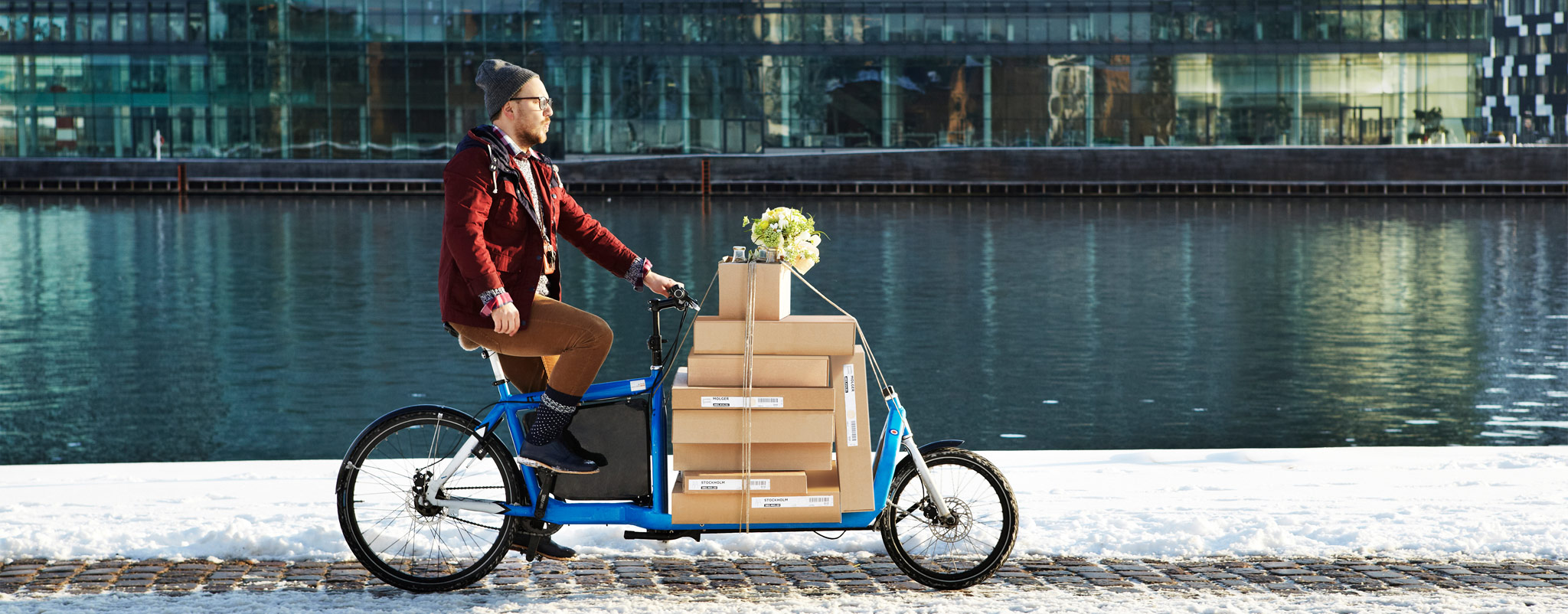 A man on a cargo bike loaded with IKEA packages.