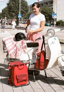 A young woman having tea at her scooter