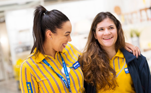 Two female IKEA co-workers  embracing each other.